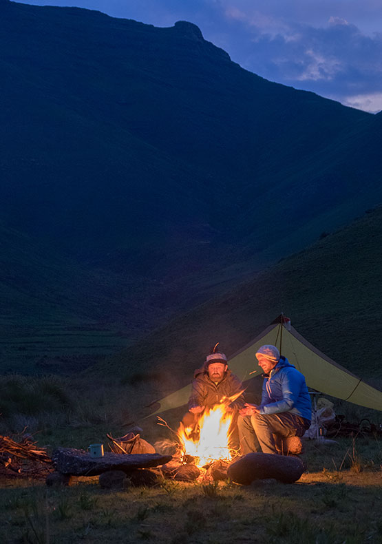 Two campers warm their hands on the fire while on the Backcountry Trek in Lesotho