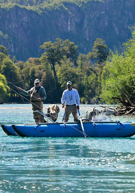 a fly fisher fights a trout from a drift boat while his guide instructs him at Futa Lodge Patagonia, Argentina