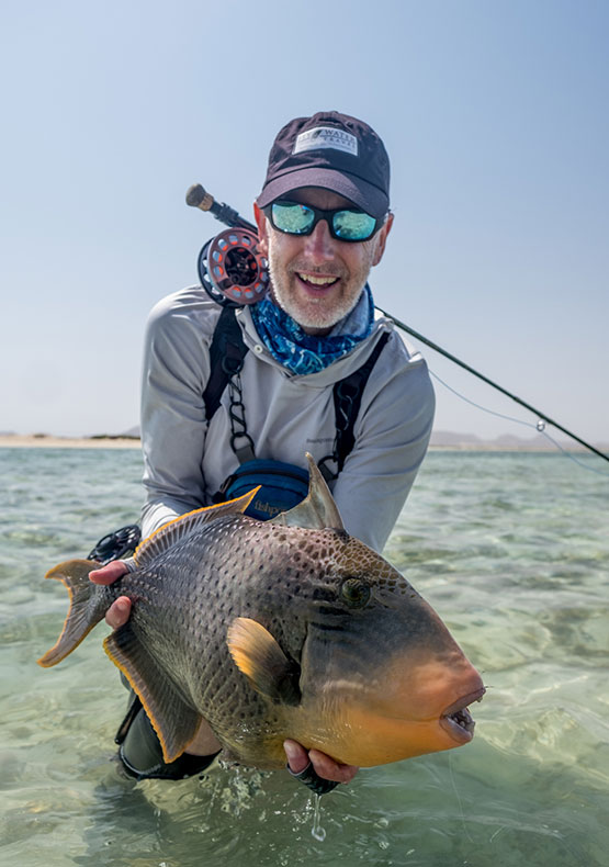 a saltwater fly angler holding a yellow-margin triggerfish caught on the Nubian flats deep south tour, in the Red Sea Sudan