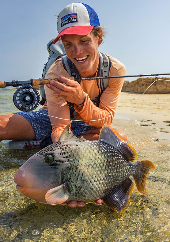 a stoked fly fisherman holds a yellow-margin triggerfish in shallow water during a tour to the Nubian Flats Northern Season, Red Sea Sudan