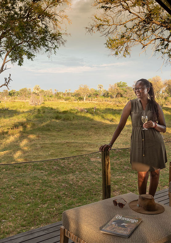 A women stands with a drink in hand while relaxing on the deck at Gomoti Private camp in the Okavango delta, Botswana