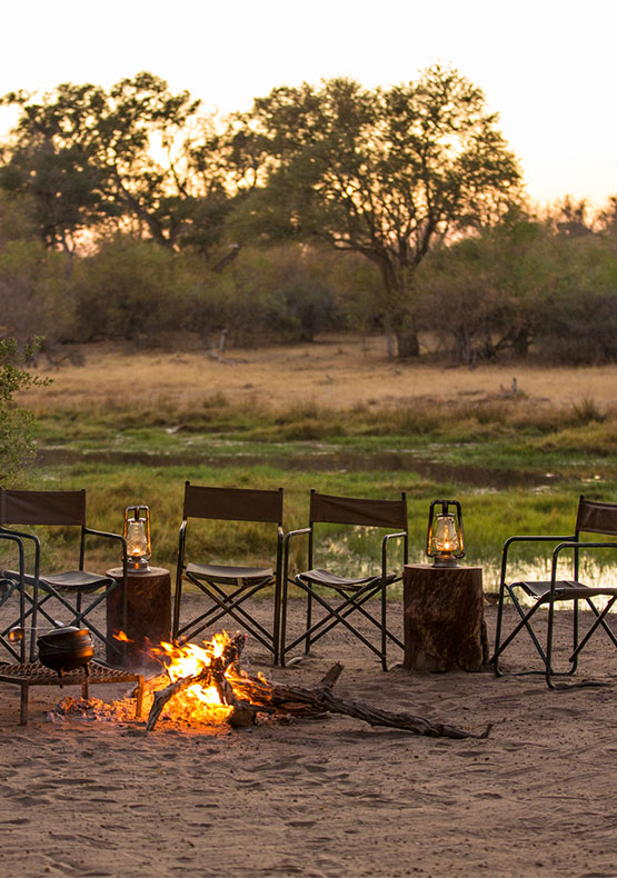 some camp chairs facing a fire with the bushveld in the background at Machaba Camp in the Okavango delta, Botswana