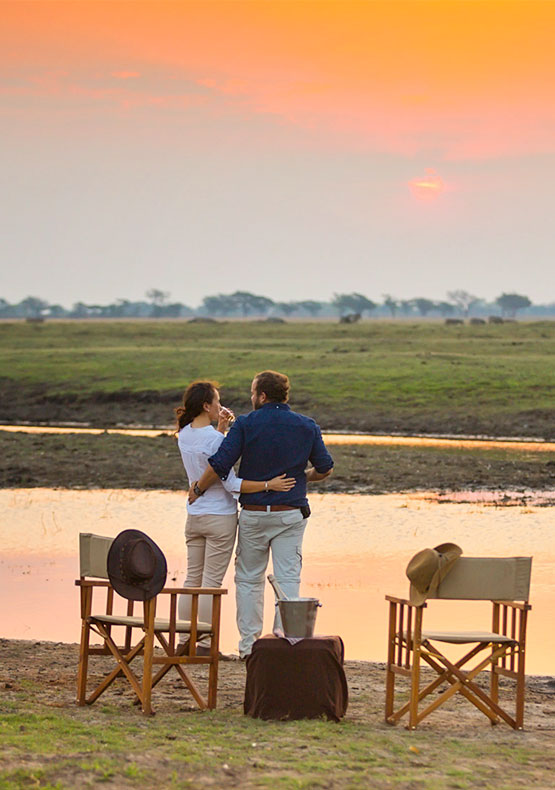 a couple enjoy a sundowner drink overlooking the safari plains at Ngoma Safari lodge, in Chobe Botswana