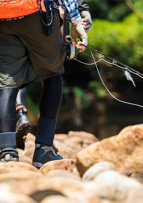 A fly fisherman holding a rod while walking boulders in Bolivia