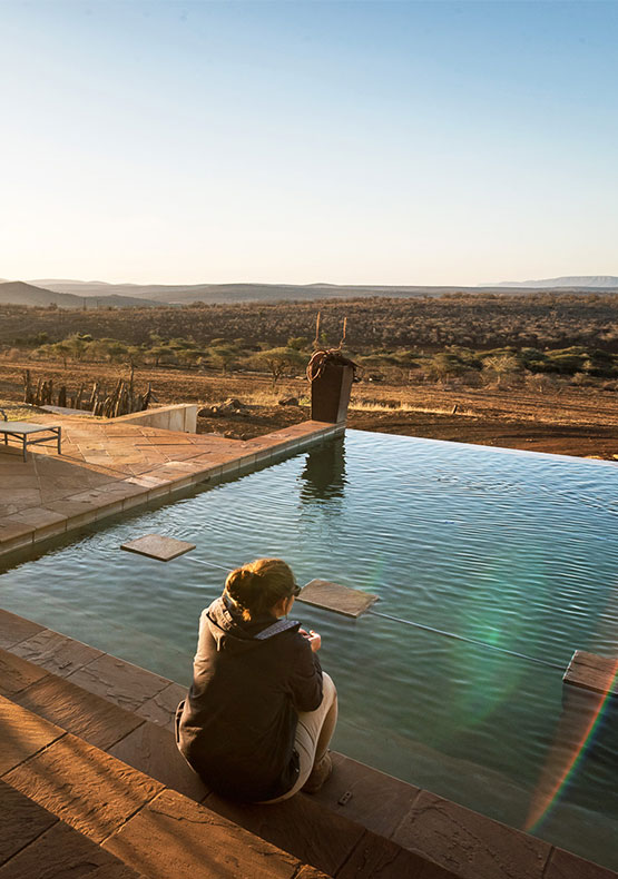 a woman looking over the pool and onto the wide open savanna at Bayete Zulu Homestead, South Africa