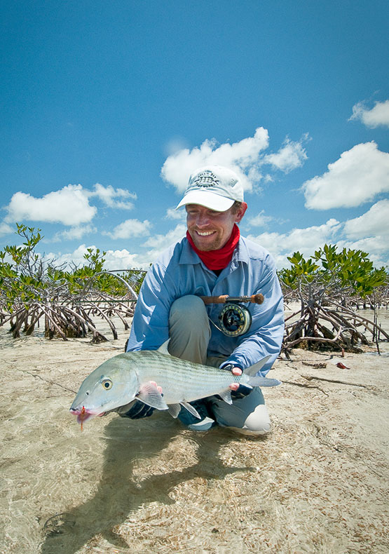 A saltwater fly fisherman posing with a bonefish caught in the mangroves in the Bahamas