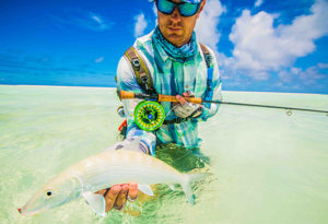 an angler shows a bonefish with a fly in its mouth before release on Alphonse Island, Seychelles