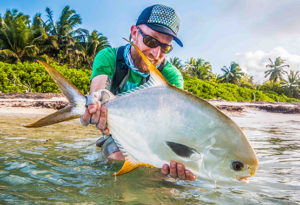 a fly angler holds a permit toward the camera prior to release at Alphonse Island, Seychelles