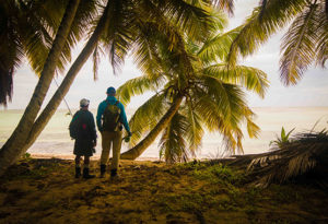 an angler and a guide stand on the beach amongst the palm trees looking onto the saltwater flats they are about to fish at Alphonse Island, Seychelles