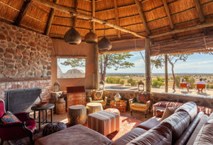 an inside view of the lounge area looking out toward the deck and bushveld at Deka Camp in Hwange National Park, Zimbabwe