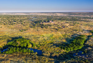 an aerial view of the river and bushveld that surround Deka Camp in Hwange National Park, Zimbabwe. The lodge can be seen in the background