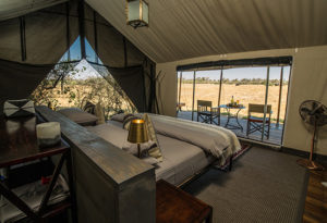 the luxury accommodation and double bed looking out onto the private deck & open safari plains at Machaba Camp, Okavango Delta Botswana