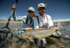 a fly fishing guide holds a trophy brown trout just above the river while the lady fly fisher sits behind holding a net at Northern Patagonia Lodge, Argentina