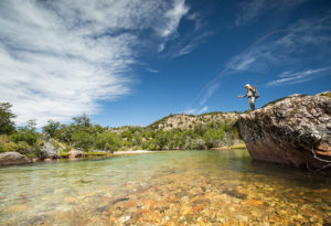 a lady fly angler stands up on a rock above the crystal clear river while she make a cast at Northern Patagonia Lodge, Argentina