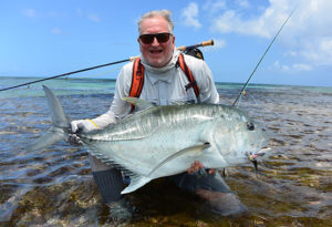 a smiling fly fisherman rests on one knee in the water as he lifts a triphy GT. The fly is in the fish's mouth and was caught on Providence Atoll, Seychelles