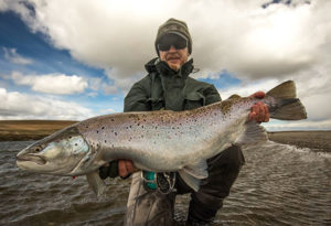 a spey angler wearing a beanie poses with a trophy sea trout caught on fly at Villa Maria lodge, Argentina