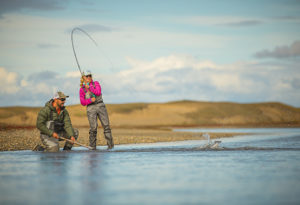 a female fly angler bends her fly rod while landing a sea trout while her guide kneels ready to net the fish at Villa Maria lodge, Argentina