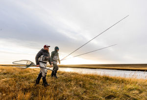 two spey anglers walk toward the river with the sun setting behind them at Kau Taupen lodge, Argentina