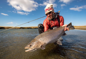 a fly fisherman poses with a trophy sea run brown trout in the river shallows before release at Kau Taupen lodge, Argentina
