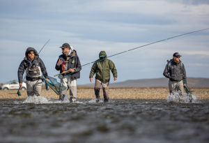 a group of spey rod anglers wade across the river in waders to start fishing for sea trout at Kau Taupen lodge, Argentina